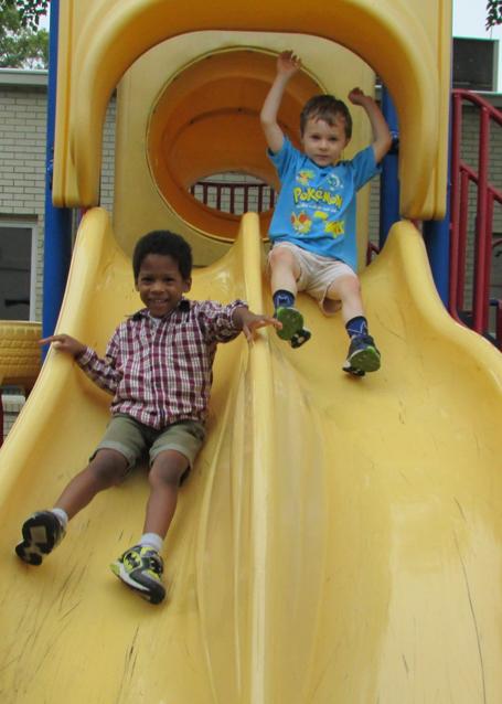2 kids sliding down a slide at Apostle Learning Center